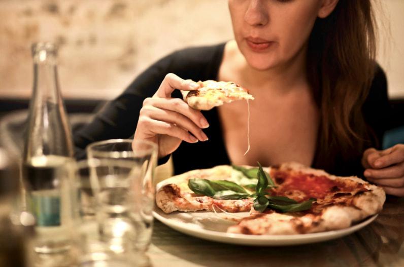 Une cliente déguste sa pizza à Bella Pizza